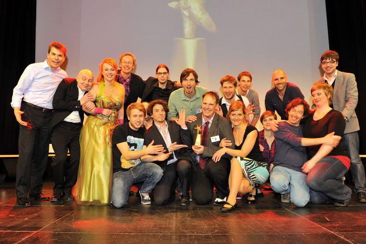 Dave Luza, Gewinner des Goldenen ImproSterns 2013, umrahmt von allen Mitwirkenden. Foto: Thomas Bruttel